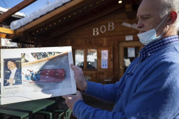 Renzo Costantini shows a picture of American bobsledder James Morgan who died in a crash on the track during the 1981 world championships, in Cortina d'Ampezzo, Italy, Wednesday, Feb. 17, 2021. Costantini pines for the good old days when drivers and brakemen would come whizzing down the track on one side of the café and then hop off their sleds on the other side and come in for a shot of espresso, a vin brulé or perhaps even a taste of the local grappa. (AP Photo/Gabriele Facciotti)