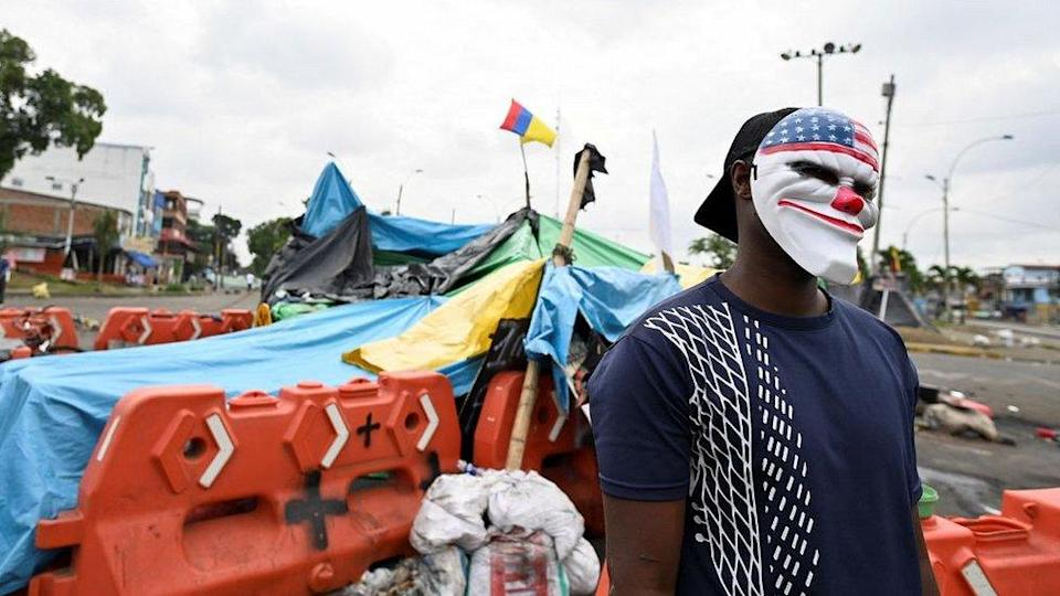 A demonstrator stands next to a barricade during a protest against Colombian President Ivan Duque's government, in Cali, on May 29, 2021