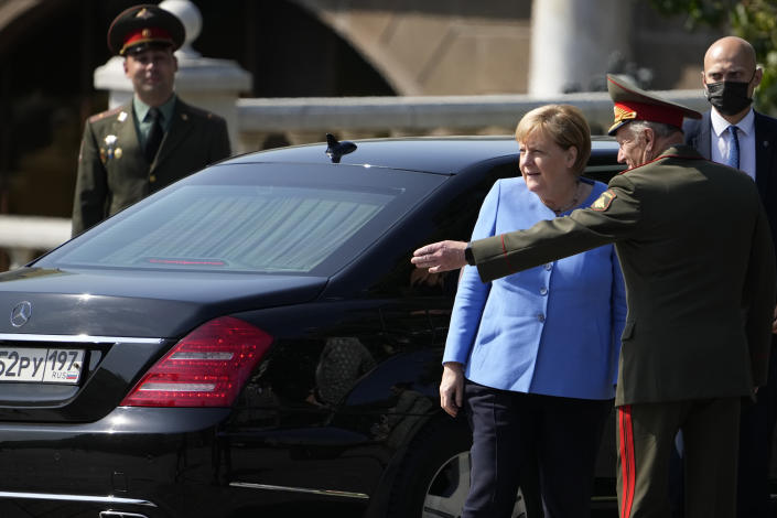 German Chancellor Angela Merkel, center, arrives for a wreath laying ceremony at the Tomb of Unknown Soldier in Moscow, Russia, Friday, Aug. 20, 2021, prior to talks with Russian President Vladimir Putin. The talks between Merkel and Putin are expected to focus on Afghanistan, the Ukrainian crisis and the situation in Belarus among other issues. (AP Photo/Alexander Zemlianichenko, Pool)