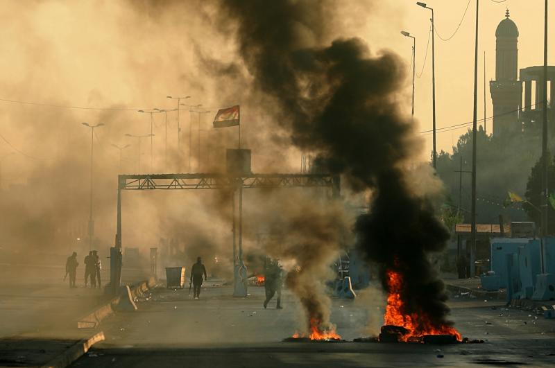 Iraqi security forces fire tear gas to disperse anti-government protesters who set fires and close a street during a demonstration in Baghdad, Iraq, Saturday, Oct. 5, 2019. The spontaneous protests which started Tuesday in Baghdad and southern cities were sparked by endemic corruption and lack of jobs. Security forces responded with a harsh crackdown, with dozens killed. (AP Photo/Hadi Mizban)