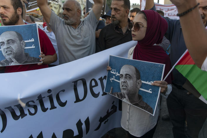 """Demonstrators carry posters with pictures of Palestinian Authority outspoken critic Nizar Banat and reads """"your voice is heard,"""" during a rally protesting his death in the West Bank city of Ramallah, Saturday, July. 17, 2021. The family of the political activist who died in the custody of Palestinian security forces last month, on Saturday accused the Palestinian Authority of trying to cover up his death. (AP Photo/Nasser Nasser)"""