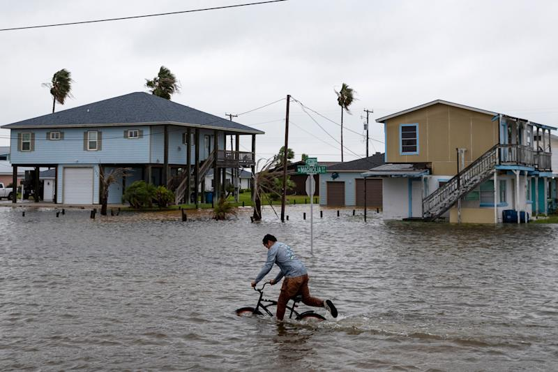 A boy rides his bike down South Magnolia Street in Rockport, Texas, as Tropical Storm Beta approaches on Sept. 21, 2020.