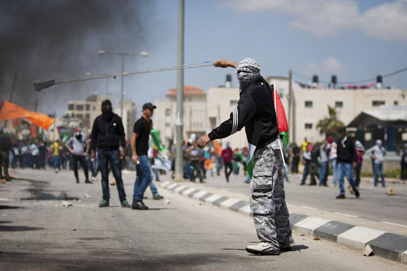 A masked Palestinian uses a slingshot to hurl stones toward Israeli soldiers during a protest calling for the release of Palestinian prisoners held in Israeli jails, outside Ofer, an Israeli military prison near the West Bank city of Ramallah, Friday, April 4, 2014. (AP Photo/Majdi Mohammed)