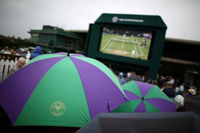 LONDON, ENGLAND - JUNE 27: Spectators wait under umbrellas for play to resume on day four of the Wimbledon Lawn Tennis Championships at the All England Lawn Tennis and Croquet Club on June 27, 2013 in London, England. Play has been disrupted on some courts due to rain. (Photo by Peter Macdiarmid/Getty Images)