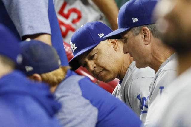 Los Angeles Dodgers manager Dave Roberts works in the dugout in the seventh inning of a baseball game against the Cincinnati Reds, Tuesday, Sept. 11, 2018, in Cincinnati. (AP Photo/John Minchillo)