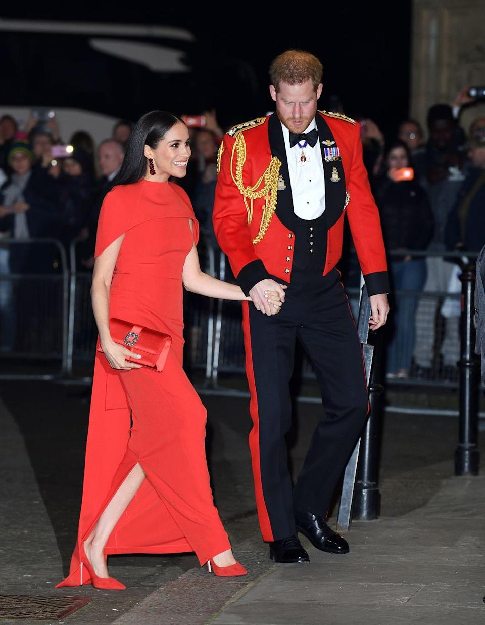 """<p>Prince Harry was seen holding his wife's hand and helping her up the steps of the Albert Hall in London on March 7 as they made their way into the <a href=""""https://www.elle.com/uk/life-and-culture/a31269596/meghan-markle-prince-harry-mountbatten-festival-music/"""" rel=""""nofollow noopener"""" target=""""_blank"""" data-ylk=""""slk:Mountbatten Music Festival"""" class=""""link rapid-noclick-resp"""">Mountbatten Music Festival</a>. </p><p>Meghan wore a beautiful full-length crepe, caped, red dress <a href=""""https://www.safiyaa.com/products/kalika-long-dress"""" rel=""""nofollow noopener"""" target=""""_blank"""" data-ylk=""""slk:by Safiyaa"""" class=""""link rapid-noclick-resp"""">by Safiyaa</a> for the occasion. </p>"""