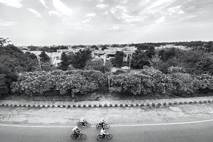 Cyclists on a highway connecting Delhi to Mumbai