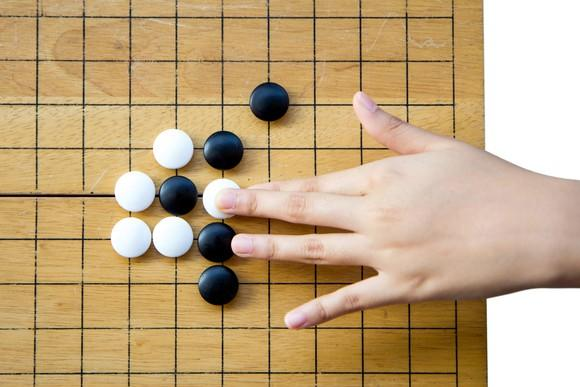 A hand placing a white Go piece on a Go board