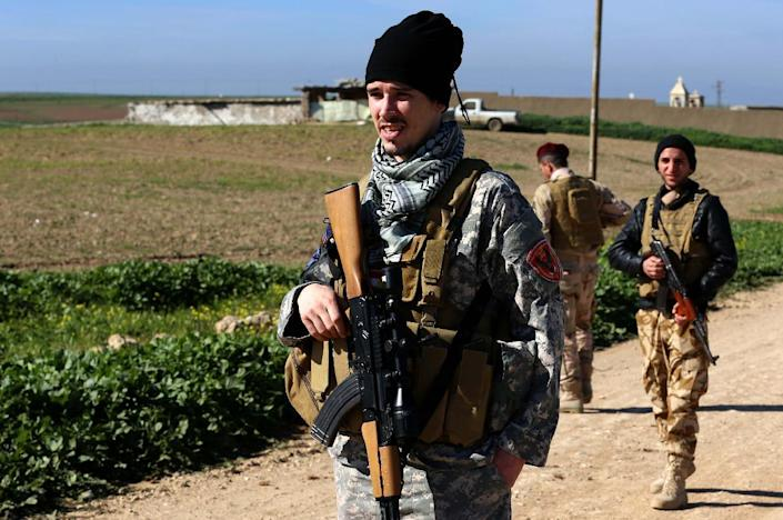 """US national """"Brett"""" (L) patrols a road in the town of Al-Qosh, in northern Iraq, where he is fighting Islamic State (IS) militants alongside Christian militia group Dwekh Nawsha (AFP Photo/Safin Hamed)"""