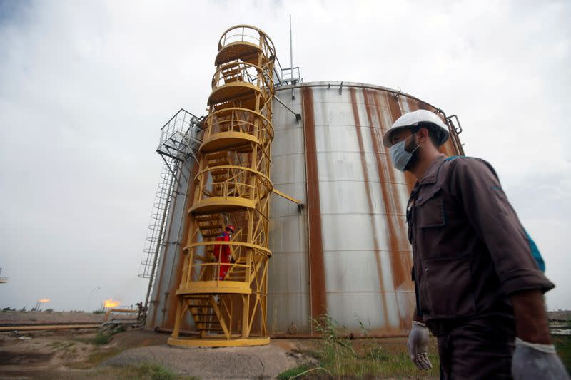 FILE PHOTO: A worker wears a protective mask, following an outbreak of coronavirus, at Nahr Bin Umar oil field, north of Basra