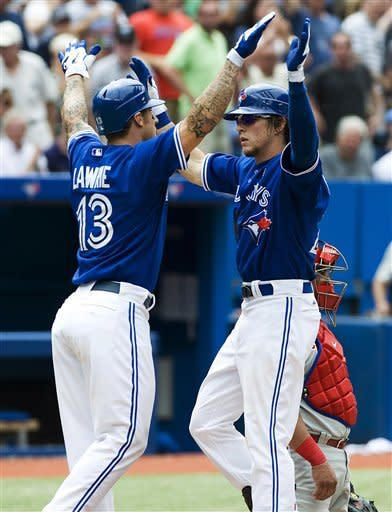Toronto Blue Jays' Colby Rasmus, right, celebrates a two-run home run with Brett Lawrie who also scored against the Philadelphia Phillies during the fifth inning of a baseball game, Sunday, June 17, 2012, in Toronto. (AP Photo/The Canadian Press, Aaron Vincent Elkaim)