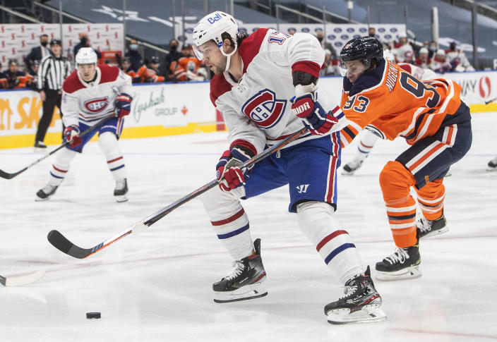 Edmonton Oilers' Ryan Nugent-Hopkins (93) chases Montreal Canadiens' Josh Anderson (17) during first-period NHL hockey game action in Edmonton, Alberta, Saturday, Jan. 16, 2021. (Jason Franson/The Canadian Press via AP)