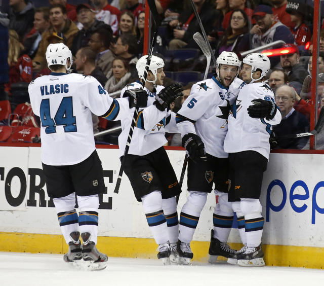 San Jose Sharks center Tyler Kennedy, right, celebrates his goal with defenseman Marc-Edouard Vlasic (44), center Andrew Desjardins (10) and defenseman Jason Demers (5) during the first period of an NHL hockey game against the Washington Capitals, Tuesday, Jan. 14, 2014, in Washington. (AP Photo/Alex Brandon)