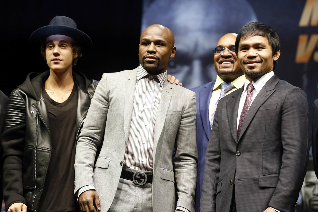 """Eleven-time, five-division world boxing champion Floyd """"Money"""" Mayweather (2nd L) and eight-division world champion Manny """"Pac-Man"""" Pacquiao (R) pose with Justin Bieber (L) at a news conference, ahead of their upcoming bout, in Los Angeles, California March 11, 2015.  REUTERS/Lucy Nicholson (UNITED STATES - Tags: SPORT BOXING ENTERTAINMENT)"""