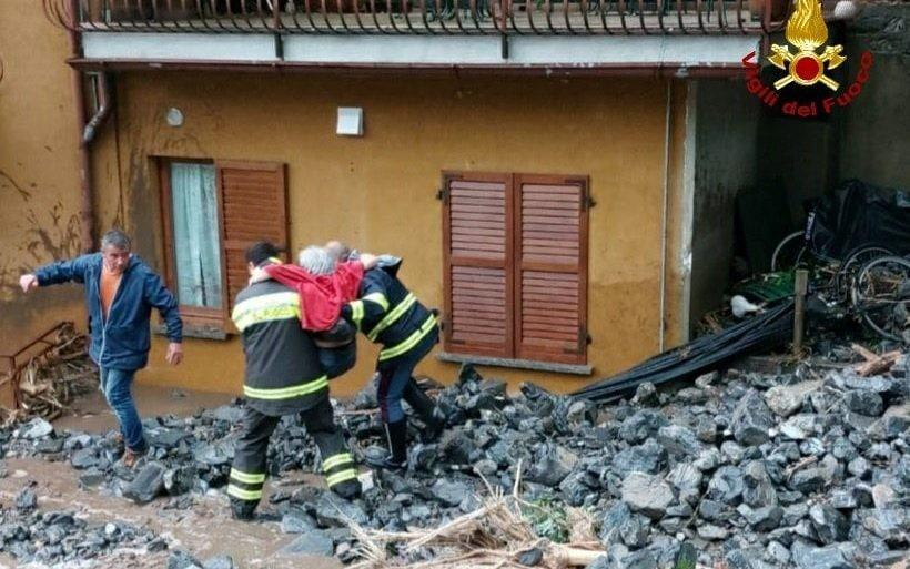 A woman is rescued by members of the fire brigade in an area affected by floods caused by heavy rainfalls near Lake Como in Brienno - VIGILI DEL FUOCO /via REUTERS