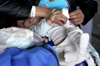 A woman dressed a baby at a respite center hosted by a humanitarian group after they were released from U.S. Customs and Border Protection custody, Saturday, March 20, 2021, in Brownsville, Texas. A surge of migrants on the Southwest border has the Biden administration on the defensive. The head of Homeland Security acknowledged the severity of the problem Tuesday but insisted it's under control and said he won't revive a Trump-era practice of immediately expelling teens and children. An official says U.S. authorities encountered nearly double the number children traveling alone across the Mexican border in one day this week than on an average day last month. (AP Photo/Julio Cortez)