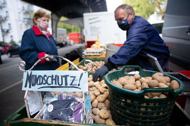 A market trader in Hamburg, Germany sells handmade facemasks as the Ifo predicts the German economy will shrink by 6.6% this year due to COVID-19. (Christian Charisius/picture alliance via Getty Images)