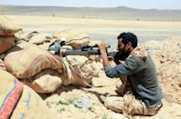 A fighter with forces loyal to Yemen's Saudi-backed government holds a position against Huthi rebels in Yemen's northeastern province of Marib, on April 6