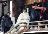 """Japan's Emperor Naruhito, in a white robe, leaves after praying at """"Kashikodokoro"""", one of three shrines at the Imperial Palace, in Tokyo, Tuesday, Oct. 22, 2019. Emperor Naruhito visited three Shinto shrines at the Imperial Palace before proclaiming himself Japan's 126th emperor in an enthronement ceremony. (Kyodo News via AP)"""