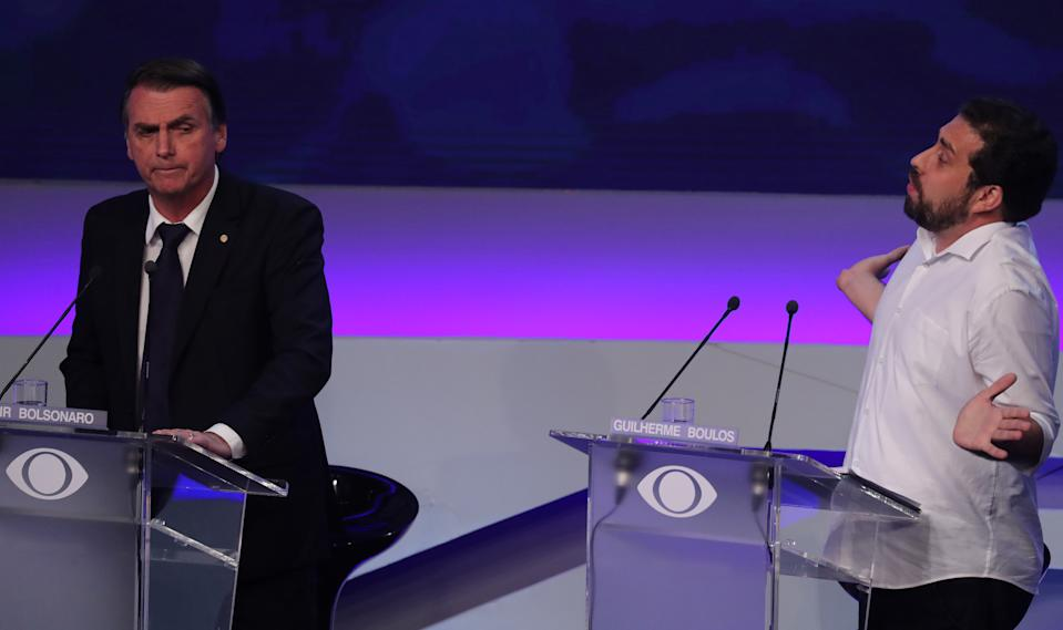 Presidential candidate Guilherme Boulos of the Socialism and Freedom Party (PSOL) speaks next to candidate Jair Bolsonaro of the Party for Socialism and Liberation (PSL) during their first television debate at the Bandeirantes TV studio in Sao Paulo August 10, 2018. REUTERS/Paulo Whitaker