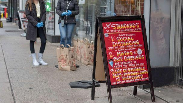 PHOTO: A sign listing new guidelines for social distancing, face coverings, and reusable bags is displayed in front of a Trader Joe's amid the coronavirus pandemic, April 24, 2020, in New York. (Alexi Rosenfeld/Getty Images)