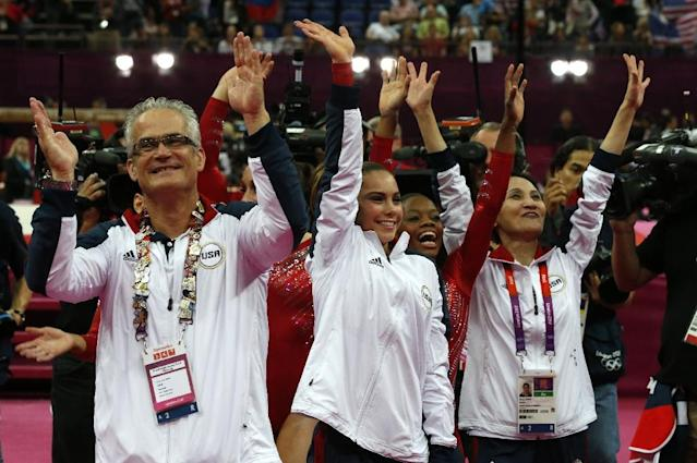 US gymnasts Gabrielle Douglas (C), Mckayla Maroney (2D-L), coaches Jenny Zhang (R) and John Geddert (L) celebrate winning gold in the women's team of the artistic gymnastics event of the London Olympic Games on July 31, 2012 (AFP Photo/-)