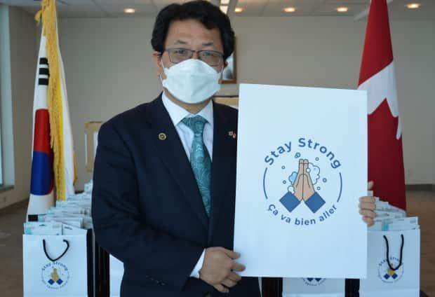 Consul General Lee Yun-je stands in front of bags of medical masks before they are sent out from the South Korean consulate in Montreal. (Submitted by Consulate General of the Republic of Korea in Montreal - image credit)