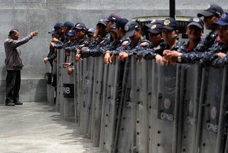 Venezuelan National Police members stand in line near the National Assembly building in Caracas