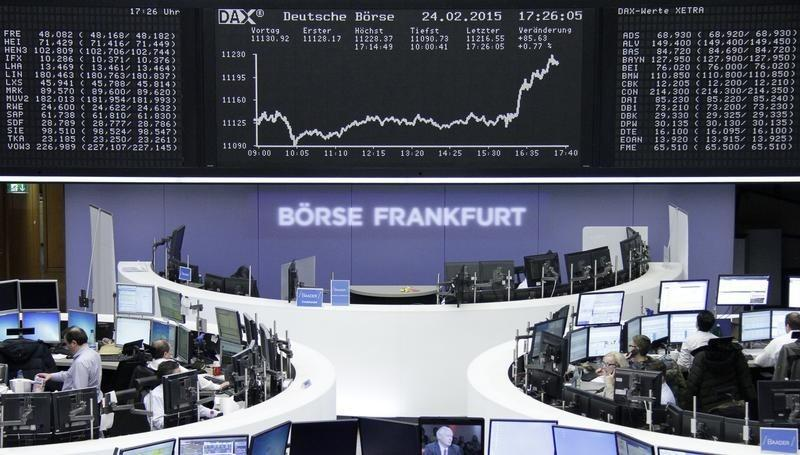 Traders are pictured at their desks in front of DAX board at Frankfurt stock exchange