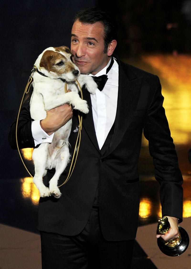 """FILE - In this Feb. 26, 2012 file photo, actor Jean Dujardin holds Uggie the dog after accepting the Oscar for best picture  for """"The Artist"""" during the 84th Academy Awards in the Hollywood section of Los Angeles. Uggie, the Jack Russell terrier who appeared in films like the Oscar-winning """"The Artist,"""" """"The Descendants"""" and """"Water for Elephants,"""" has a memoir coming. Gallery Books, an imprint of Simon & Schuster, announced Friday that """"Uggie: My Story"""" will come out in October. His tale of tails will be transcribed by biographer and presumed dog whisperer Wendy Holden. (AP Photo/Mark J. Terrill, file)"""