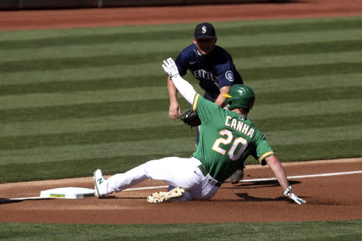 Oakland Athletics' Mark Canha (20) slides safely into third as Seattle Mariners' Kyle Seager applies the tag during the first inning of the first baseball game of a doubleheader in Oakland, Calif., Saturday, Sept. 26, 2020. (AP Photo/Jed Jacobsohn)