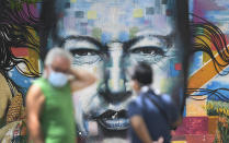 Pedestrians wearing masks to curb the spread of the new coronavirus chat in front of a mural of late President Hugo Chavez, in Caracas, Venezuela, Sunday, July 12, 2020. (AP Photo/Matias Delacroix)