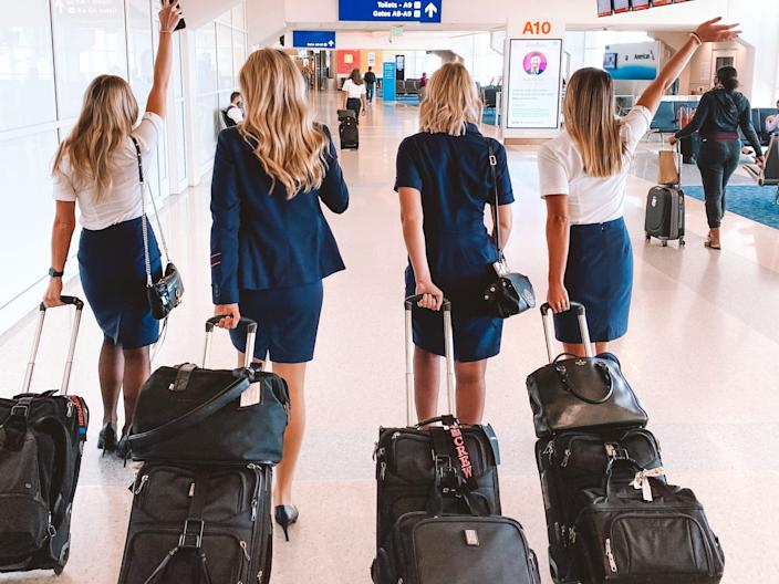 A group of flight attendants with their suitcases inside of an airport