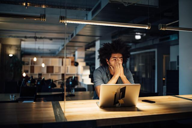 Tired businessman working late on laptop while sitting at illuminated desk in office. Photo: Getty