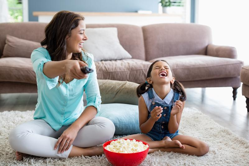 A woman and a girl share popcorn while watching TV.