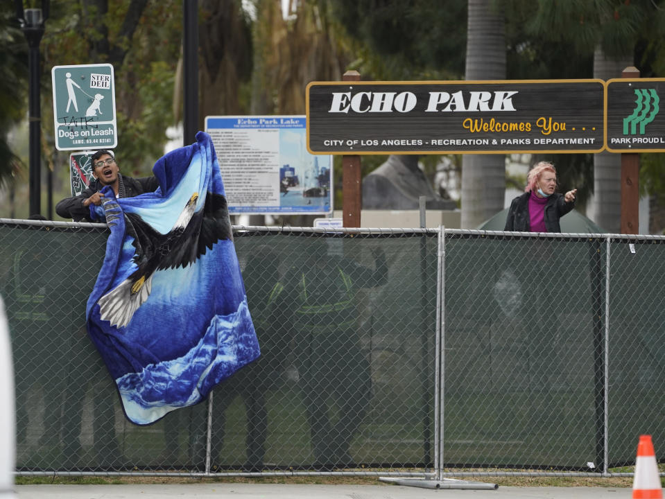 A homeless activist waves a blanket over a fence as Los Angeles City sanitation workers move inside the closed perimeter of Echo Park Lake in Los Angeles, Thursday, March 25, 2021. A newly installed fence surrounded the park Thursday after a late-night confrontation between police and vocal demonstrators who oppose the city's effort to remove a large homeless encampment and perform extensive repairs of the site. People who were already in tents at Echo Park Lake were allowed to remain overnight but were given 24-hour notice to leave, Police Chief Michel Moore said in a social media post. (AP Photo/Damian Dovarganes)