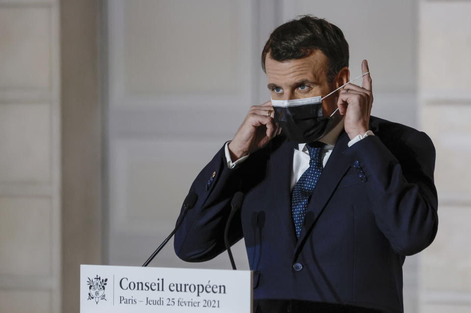 French President Emmanuel Macron takes off his mask as he arrives for a media conference after an EU Summit, via videoconference link, at the Elysee Palace in Paris, Thursday, Feb. 25, 2021. European Union leaders gathered Thursday, via videoconference link, to try to inject new energy into the 27-nation bloc's lagging coronavirus vaccination effort as concern mounts that new variants might spread faster than authorities can adapt. (Thomas Coex, Pool via AP)