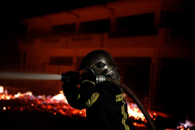 <p>A firefighter holds a hose as a wildfire burns at the village of Mati, near Athens, Greece, July 23, 2018. (Photo: Alkis Konstantinidis/Reuters) </p>
