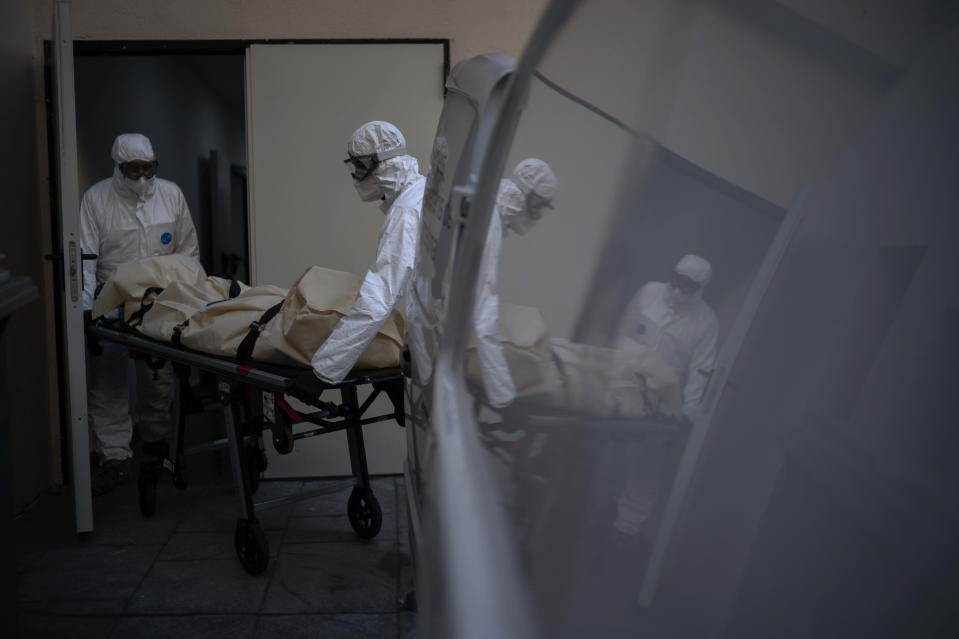 Mortuary workers pick up the body of a COVID-19 victim from a nursing home in Barcelona, Spain, Thursday, Nov. 19, 2020. After successfully bringing the daily death count down from over 900 in March to single digits by July, Spain has seen a steady uptick that brought deaths back to over 200 a day this month. With that relapse, the body collectors have returned to making the rounds of hospitals, homes and care facilities. (AP Photo/Emilio Morenatti)