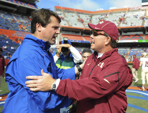 Florida coach Will Muschamp, left, meets with Florida State coach Jimbo Fisher, right prior the kick-off of an NCAA college football game Saturday, Nov. 30, 2013 in Gainesville, Fla. (AP Photo/Phil Sandlin)