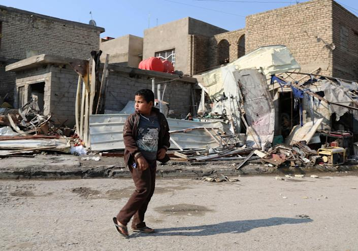 A boy walks amid rubble a day after a bombing in the Abu Disher neighborhood of southern Baghdad, Iraq, Tuesday, Jan. 21, 2014. Violence spiked in Iraq after the government staged a deadly crackdown on a Sunni protest camp last April. Militants have also targeted civilians, particularly in Shiite areas of Baghdad, with coordinated car bombings and other deadly attacks. (AP Photo/Karim Kadim)