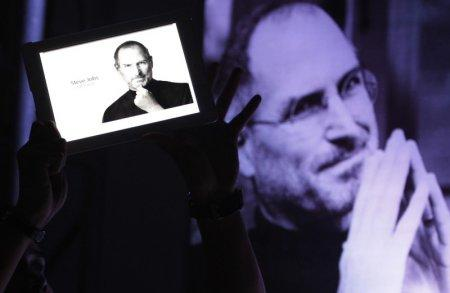 FILE PHOTO - A man holds an iPad displaying a photo of Steve Jobs during a 'Steve Jobs Day' memorial day event in Manila October 14, 2011. REUTERS/Romeo Ranoco