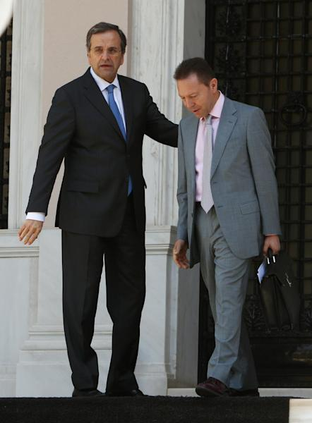 """Greece's Prime Minister Antonis Samaras, left, and Finance Minister Yannis Stournaras are seen after a meeting with the heads of the two junior coalition parties at Maximos Mansion in Athens, Thursday, Sept. 27, 2012. Stournaras says the heads of the three parties in the governing coalition have reached a """"basic agreement"""" on an austerity package for 2013-14.The cuts are essential if Greece is to continue receiving funds from international emergency loans. (AP Photo/Thanassis Stavrakis)"""
