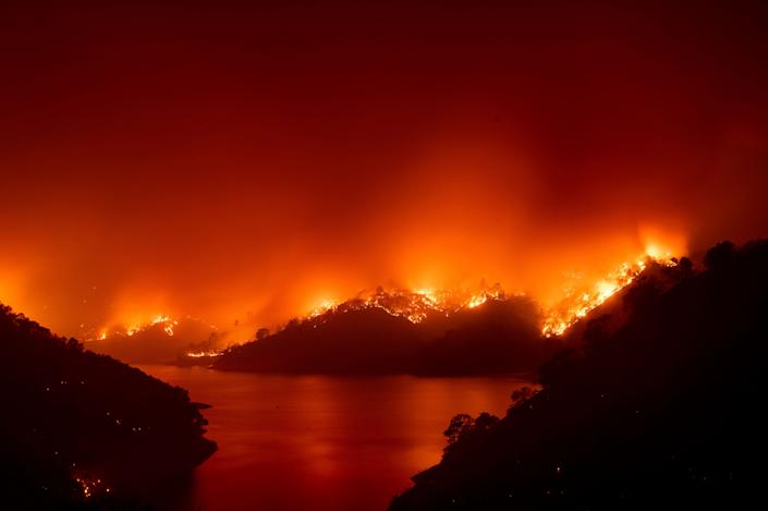 Flames from the wildfire designated as the LNU Lightning Complex are seen around Lake Berryessa in Napa County, California on Wednesday. Fire crews across the region have scrambled to contain dozens of wildfires sparked by lightning strikes. (Photo: ASSOCIATED PRESS)