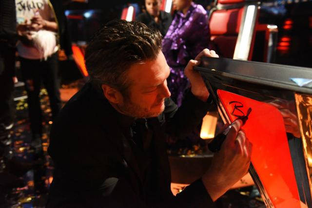 Blake Shelton autographs a classic <em>Voice</em> chair. (Photo: NBC)