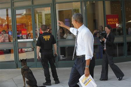 Obama waves at people after he and Biden bought lunch at a sandwich shop near the White House in Washington