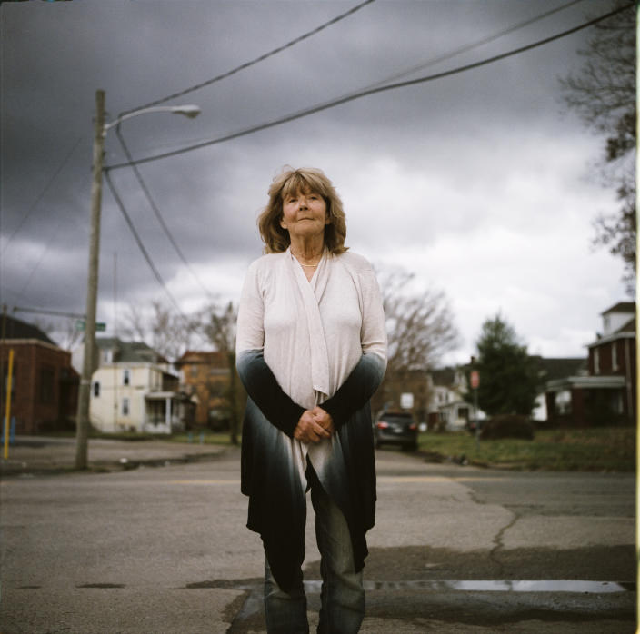 "In this photo made with a medium format film camera, Sue Howland, a member of the Quick Response Team that tries to track down everyone who overdoses to offer help, stands for a portrait in Huntington, W.Va., Thursday, March 18, 2021. The 62-year-old peer recovery coach nearly drank herself to death years ago, so she can relate to the madness her clients are facing. ""We're going to love them until they learn to love themselves. We're going to love them back to life,"" said Howland, who's been sober now for 10 years. ""The things that bring me the greatest pleasures now are priceless: waking up in the morning, the sunrise, being able to walk on a beach, hearing the birds sing, seeing a rainbow, seeing raindrops fall in puddles, seeing somebody smile. I tell people when they come into treatment, I say you're giving yourself a gift money can't buy."" (AP Photo/David Goldman)"