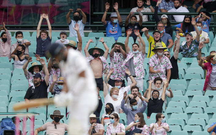 """Spectators perform a """"Mexican wave """" during play on day two of the third cricket test between India and Australia at the Sydney Cricket Ground, Sydney, Australia, Friday, Jan. 8, 2021. (AP Photo/Rick Rycroft)"""