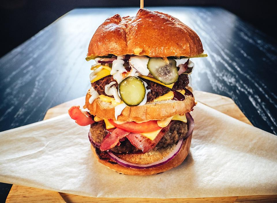 huge burger with multiple layers of toppings
