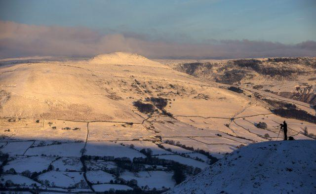 A photographer takes a picture near Mam Tor in Derbyshire's Peak District (Peter Byrne/PA)